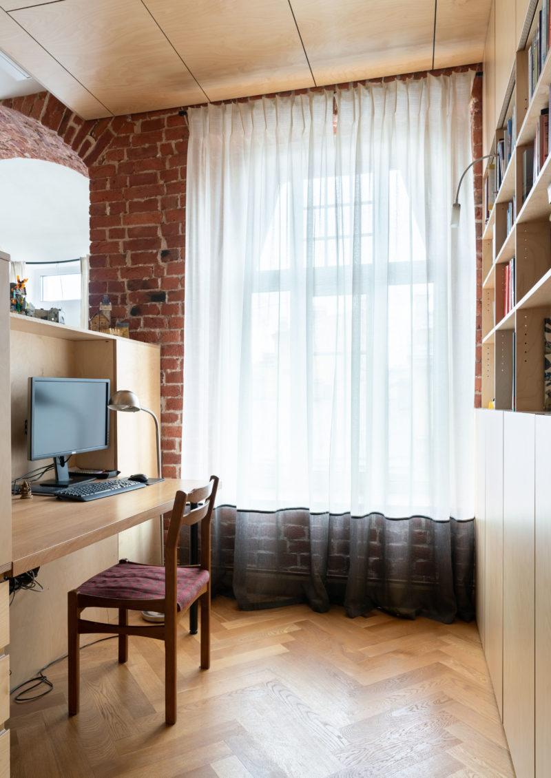 рабочая зона со столом и книжным стеллажом около окна